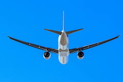 Jet airliner flying under blue sky Stock Image