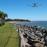 Jet Airliner Flying in an vibrant blue coloured tropical sky. Colourful coastal landscape seascape, scenic view of a commercial passenger jet airliner flying stock images
