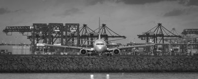 Jet airliner turning in front of industrial port Stock Photos