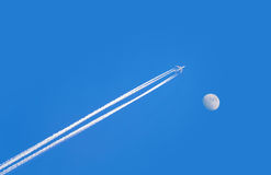 Jet airplane on blue sky with moon Stock Images