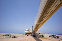 Jet Airplane connected with a passenger jetway, Stock Images