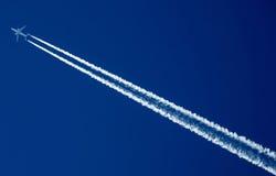 Jet Airplane contrails i bakgrund för blå himmel Fotografering för Bildbyråer