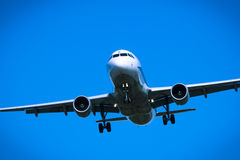 Jet airplane flying overhead close-up Royalty Free Stock Photos