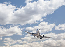 Jet Airplane Landing com nuvens dramáticas atrás Foto de Stock Royalty Free