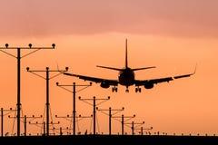Jet Airplane Landing en la puesta del sol Foto de archivo libre de regalías