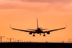 Jet Airplane Landing en la puesta del sol Fotografía de archivo