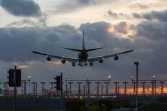 Jet Airplane Landing en la puesta del sol Imagen de archivo