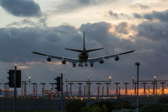 Jet Airplane Landing at Sunset. A jet airplane coming in for a landing on an airport runway Heathrow airport Stock Image
