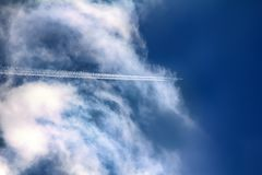 Jet airplane in sky. Air routes by white vapor in flight stock photography