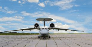 Jet airplane with turbojet engines and radar antenna. Front view of a jet plane with turbojet engines and radar antenna on tail at parking against of blue cloudy Stock Photo