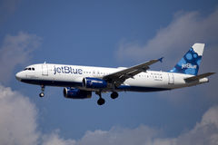 Jet Blue airline passenger jet (Airbus A320). Coming in for a landingin West Palm Beach, Florida. With Devil with the blue dress on on the plane below the Royalty Free Stock Image
