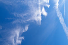 Jet in the blue cloudy sky Royalty Free Stock Image