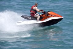 Jet Boat. A man riding a late model jet boat. (The background has slight motion blur stock photography
