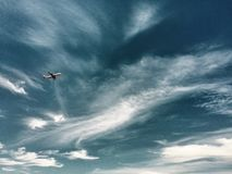 Jet in a Cirrus Sky. Virgin Airbus climbs into a sky filled with cirrus clouds Stock Photography