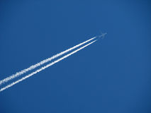 Jet and contrail. A passenger jet airplane crosses a blue sky far above leaving a double white contrail Royalty Free Stock Image