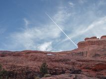 Jet Contrail over Arches National Park in Utah. A jet contrail rises above Landscape Arch at Arches National Park near Moab, Utah. Arches is red rock country stock image