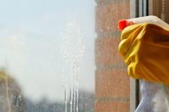 Jet détersif de bouteille de jet sur la fenêtre Photographie stock libre de droits