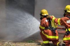 Jet d'eau d'équipe de sapeur-pompier par le tuyau d'incendie à haute pression Photographie stock libre de droits