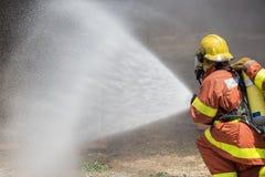 Jet d'eau de sapeur-pompier par le tuyau d'incendie à haute pression Photo libre de droits