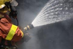 Jet d'eau de sapeur-pompier par le tuyau d'incendie à haute pression Photos stock