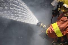 Jet d'eau de sapeur-pompier par le tuyau d'incendie à haute pression Photographie stock