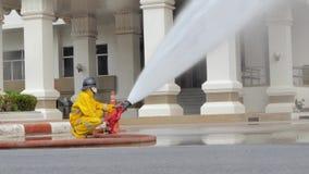 Jet d'eau de sapeur-pompier par le tuyau d'incendie à haute pression banque de vidéos