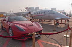 Jet de l'aviation P180 de CAEA et berline de Ferrair F12 de rouge Photographie stock libre de droits