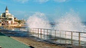 Jet des vagues éclaboussant sur la promenade menant à la plage de Tamariz dans la station touristique atlantique d'Estoril près d photos libres de droits