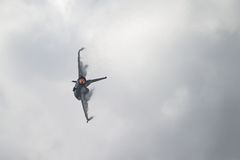 Jet F-16 con el dispositivo de poscombustión encendido y las nubes del vapor que forman en las alas Fotografía de archivo libre de regalías
