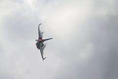 Jet F-16 con il postcombustore sopra e le nubi del vapore che si formano sulle ali fotografia stock libera da diritti