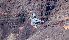 Jet Fighter Military Aircraft Flying. F-18 Navy military jet aircraft flying through canyon with canyon rock walls in background stock image