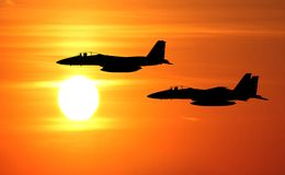 Jet fighter. Silhouette flights and sunset background Royalty Free Stock Photos