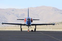 Jet fighter on tarmac. A military jet fighter on a tarmac in Reno, Nevada with a mountain backdrop and clear, blue sky Stock Image