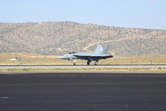 Jet fighter on tarmac in Western United States. United States military jet fighter in the Western united States in Reno, Nevada against a mountain backdrop and royalty free stock images