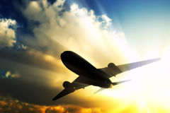 Jet in fly. A jet flies away in the rays of sun Royalty Free Stock Images
