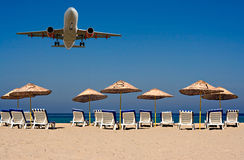 Jet flying over sunloungers on empty beach Stock Photos