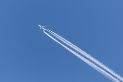 Jet with four engines in the clear sky Stock Photography