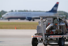 Jet Fuel Cart. On the airport ramp with plane landing in the background Royalty Free Stock Photo