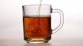 Jet of hot tea fills the glass cup. White background stock video footage