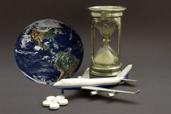 Jet Lag Concept. Miniature airplane with an hourglass, pills and globe to represent the concept of jet lag Royalty Free Stock Image