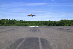 Jet landing. Jumbo jet coming into land, low perspective focus is on the plane foreground blurred Royalty Free Stock Image