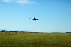 Jet Landing at Airport. A jet coming in for a landing at an airports runway out near a grassy field royalty free stock images