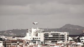 Jet landing behind buildings. Modern jet landing behind city buildings mist stock footage