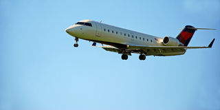 Jet with Landing Gear. A small passenger jet  makes its descent to the airport with landing gear ready Stock Photo