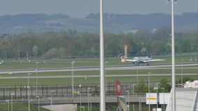 "Plane landing on Munich Airport, spring. Jet landing in Munich Airport, Germany, spring time with snow on runway. Flughafen München ""Franz Josef Strau stock footage"