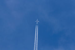 Jet leaving Trail in the Sky. Jet plane flying in the blue sky. Wake leaving trace or steam jet, viewed from below in nadir shot Royalty Free Stock Photography