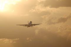 Jet liner taking off against sunrise. Large jet airplane flying into the sun Royalty Free Stock Images