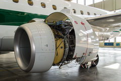 Jet Maintenance. Airplane and jet engine open and ready for maintenance inside hangar Stock Photos