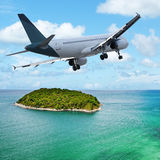 Jet maneuvering over the tropical island Stock Photo