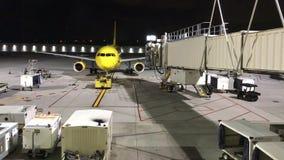 Jet op tarmac bij de brugpoort van luchthavenbenaderingen stock videobeelden